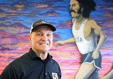 OUTLOOK PHOTO: JOSH KULLA - Jeff Kline is proud of the large mural of Steve Prefontaine that hangs on the wall at the East Wind Running Company. Every such store, he says, should have Pre on their walls.