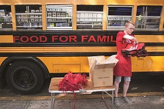 OUTLOOK PHOTO: JOSH KULLA - Centennial High student Ashton Farris gets ready to hand out bags for food.
