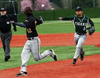 DAN BROOD - Tigard junior shortstop Manny Andrade (right) makes a throw as the Tigers have Milwaukie senior Bradley McVay caught in a rundown between first and second in Tuesday's game.