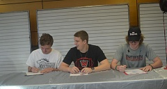 SPOKESMAN PHOTO: COREY BUCHANAN - Wilsonville football players Andrew Merrick (left), Kaden Floyd (middle) and Parker Shaw sign their letters of intent at Wilsonville High School.